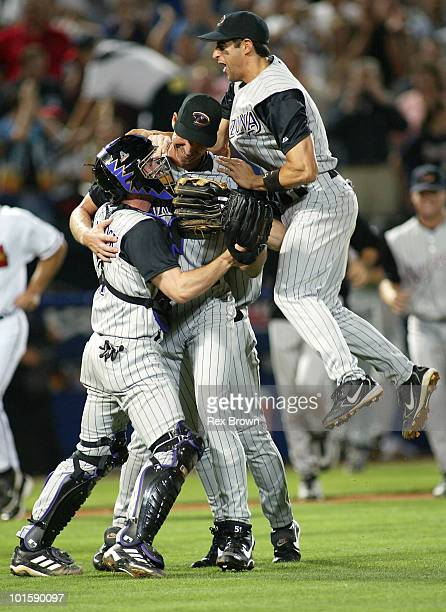 Arizona's Randy Johnson is congratulated by by catcher Robby Hammock and Alex Cintron after pitching a perfect game against the Atlanta Braves May 18...