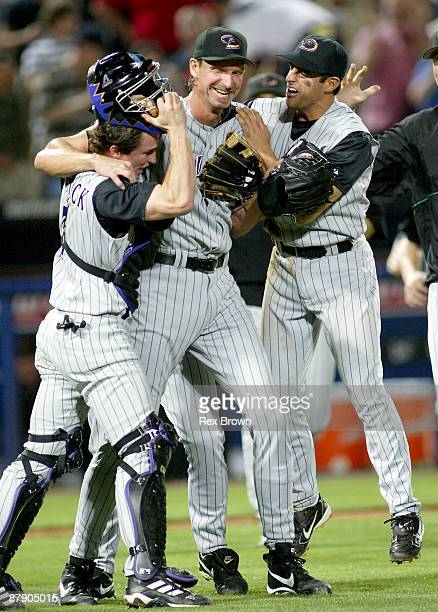 Arizona's Randy Johnson shows his excitement as he hugs teammates Robby Hammick and Alex Cintron after pitching a perfect game against Atlanta May 18...