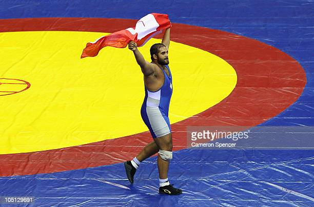 Arjan Bhullar of Canada celebrates winning the men's 120kg freestyle gold medal wrestling against Joginder Kumar of India at IG Sports Complex during...