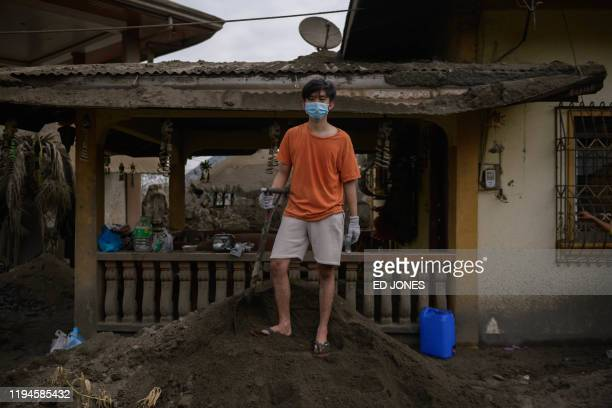 ArJay Rodriguez poses for a photo before his ashcovered home which was damaged by the eruption of the nearby Taal volcano in Buso Buso on January 19...