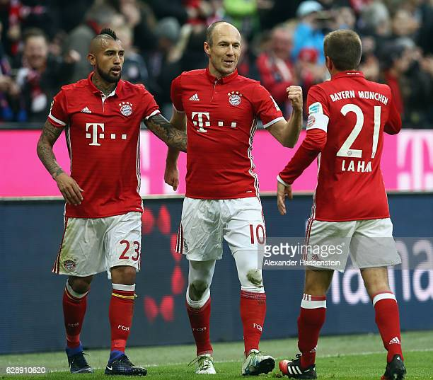 Arjen Robben 8c9 of Muenchen celebrates his team's first goal with team mates Arturo Vidal and Philipp Lahm during the Bundesliga match between...