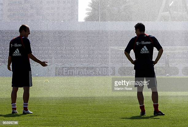 Arjen Robben and Mark van Bommel of Bayern Muenchen take a refreshment during the FC Bayern Muenchen training session at the Al Nasr training ground...