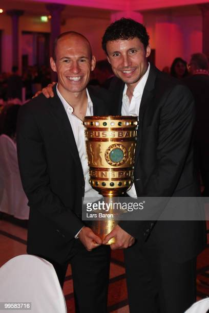 Arjen Robben and Mark van Bommel pose with the DFB Cup trophy during the Bayern Muenchen Champions Party after the DFB Cup Final match against Werder...