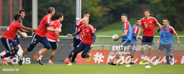 Arjen Robben and Robert Lewandowski of FC Bayern Muenchen chase their teammates during a training session at Saebener Strasse training ground on...