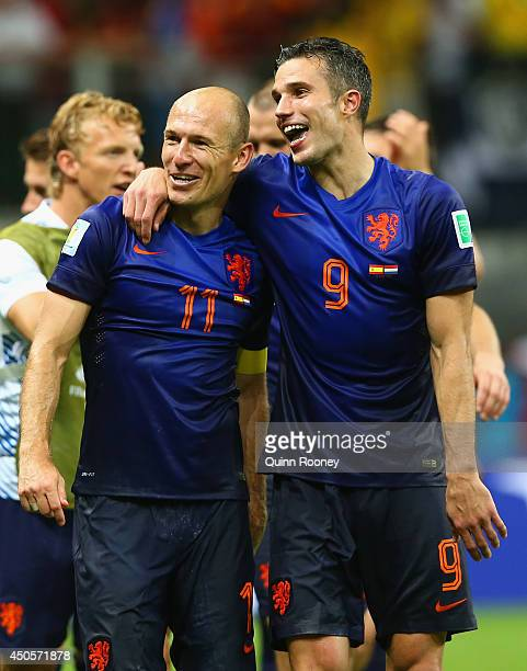 Arjen Robben and Robin van Persie of the Netherlands walk off the field after scoring two goals each and defeating Spain 51 during the 2014 FIFA...