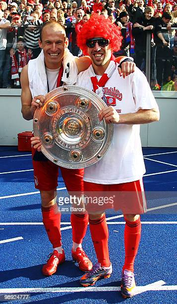 Arjen Robben and team mate Franck Ribery pose with the trophy after the Bundesliga match between Hertha BSC Berlin and FC Bayern Muenchen at Olympic...
