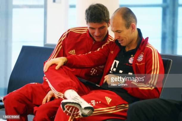 Arjen Robben and Thomas Mueller of Muenchen wait for their team's departure to the training camp in Doha at Munich airport on January 2 2012 in...