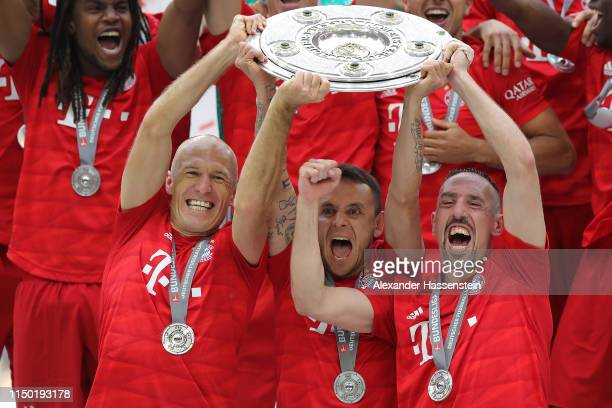 Arjen Robben Franck Ribery and Rafinha of Bayern Munich lift the trophy following the Bundesliga match between FC Bayern Muenchen and Eintracht...
