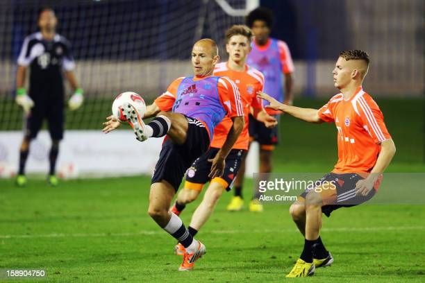 Arjen Robben is challenged by Daniel Wein during a Bayern Muenchen training session at the ASPIRE Academy for Sports Excellence on January 3, 2013 in...