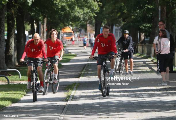 Arjen Robben Jonas Kehl and goalkeeper RonThorben Hoffmann of FC Bayern Muenchen ride bicycles during a training session near the club's Saebener...