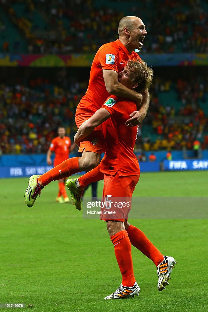 Arjen Robben jumps into the arms of Dirk Kuyt of the Netherlands as they celebrate victory in a penalty shootout during the 2014 FIFA World Cup Brazil Quarter Final match between the Netherlands and Costa Rica at Arena Fonte Nova on July 5, 2014 in Salvador, Brazil.
