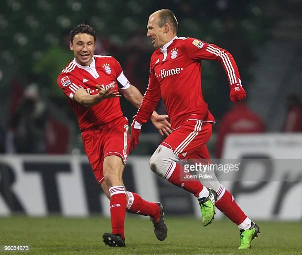 Arjen Robben of Bayern celebrates with his team mate Mark van Bommel after scoring his team's third goal during the Bundesliga match between Werder...