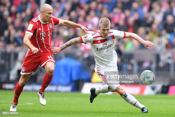 Arjen Robben of Bayern Muenchen and Rick van Drongelen of Hamburg compete for the ball during the Bundesliga match between FC Bayern Muenchen and...