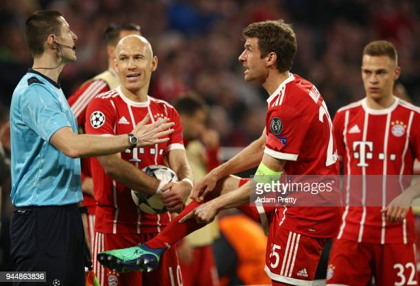 Arjen Robben of Bayern Muenchen and Thomas Mueller of Bayern Muenchen confront referee William Collum during the UEFA Champions League Quarter Final...