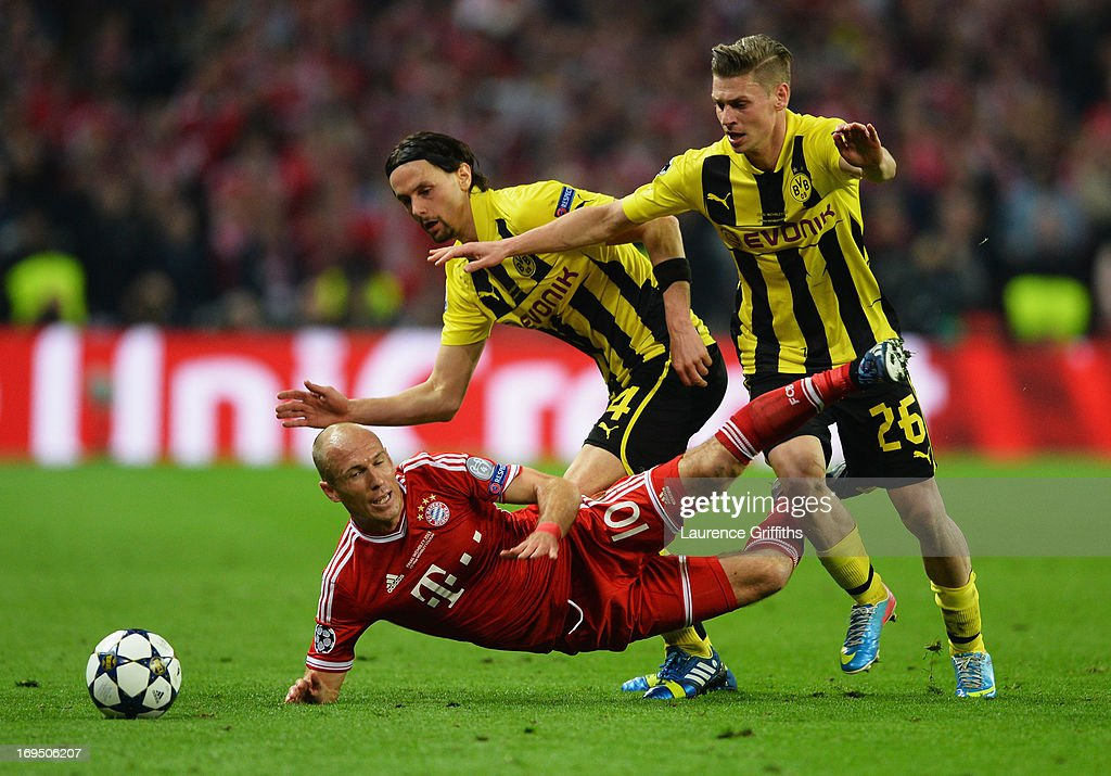 Arjen Robben of Bayern Muenchen battles with Neven Subotic (4) and Lukasz Piszczek of Borussia Dortmund (26) during the UEFA Champions League final match between Borussia Dortmund and FC Bayern Muenchen at Wembley Stadium on May 25, 2013 in London, United Kingdom.