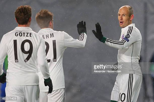 Arjen Robben of Bayern Muenchen celebrates scoring the opening goal with his team mates Philipp Lahm and Mario Goetze during UEFA Champions League...