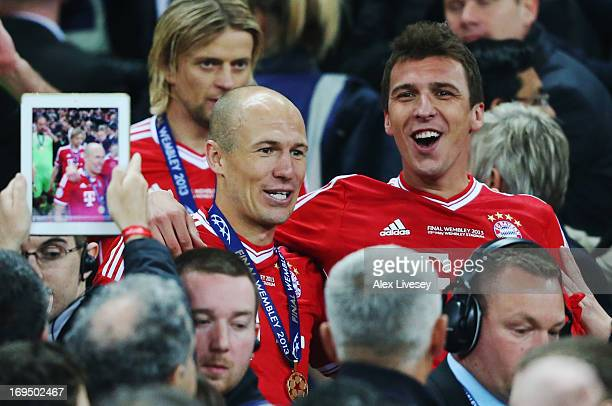 Arjen Robben of Bayern Muenchen celebrates victory with team mate Mario Mandzukic after the UEFA Champions League final match between Borussia...
