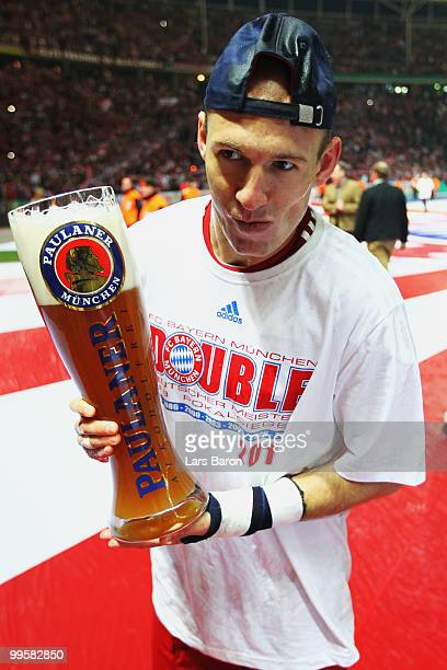 Arjen Robben of Bayern Muenchen celebrates with a beer following their team's victory at the end of the DFB Cup final match between SV Werder Bremen...