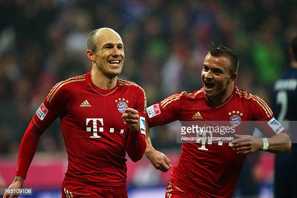 Arjen Robben of Bayern Muenchen celebrates with teammate Xherdan Shaqiri after scoring his team's fourth goal during the Bundesliga match between FC...