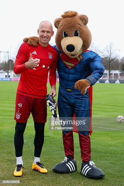 Arjen Robben of Bayern Muenchen poses with mascot Bernie dressed as Superman prior to a training session at Bayern Muenchen's training ground...