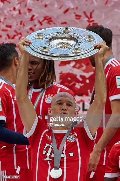 Arjen Robben of Bayern Muenchen poses with the Championship trophy in celebration of the 67th German Championship title following the Bundesliga...