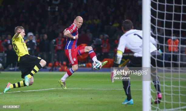Arjen Robben of Bayern Muenchen scores his team's first goal against goalkeeper Roman Weidenfeller and Lukasz Piszczek of Borussia Dortmund during...