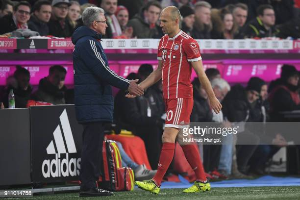 Arjen Robben of Bayern Muenchen shakes the hand of Jupp Heynckes head coach of Bayern Muechen as he comes off during the Bundesliga match between FC...