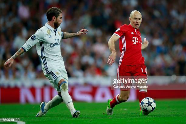 Arjen Robben of Bayern Muenchen strikes the ball behind Sergio Ramos of Real Madrid CF during the UEFA Champions League Quarter Final second leg...