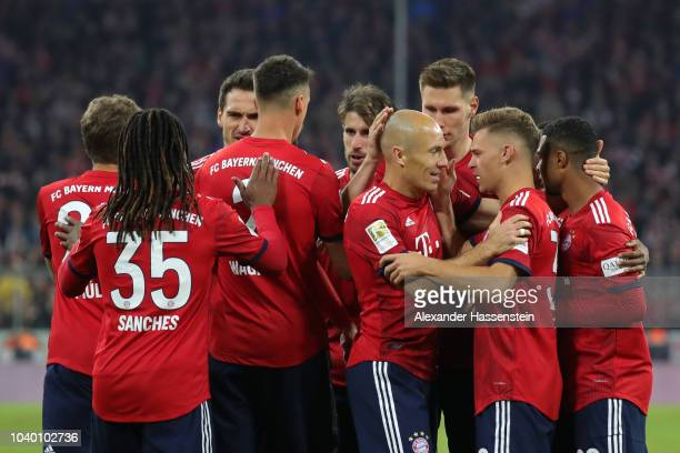 Arjen Robben of Bayern Munich celebrates with team mates after scoring his side's first goal during the Bundesliga match between FC Bayern Muenchen...