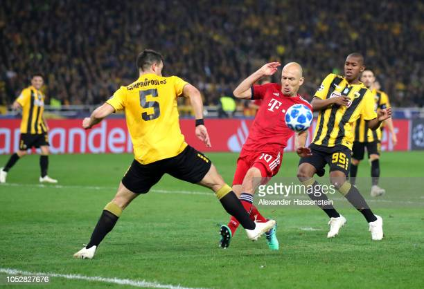 Arjen Robben of Bayern Munich is challenged by Vasilios Lampropoulos of AEK Athens and Alef of AEK Athens during the Group E match of the UEFA...