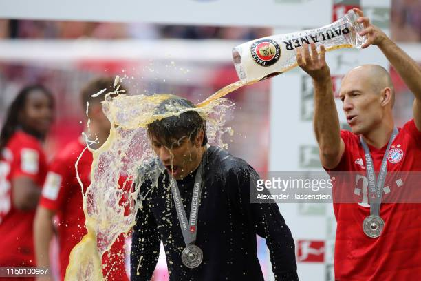 Arjen Robben of Bayern Munich pours beer over Niko Kovac Manager of Bayern Munich following the Bundesliga match between FC Bayern Muenchen and...