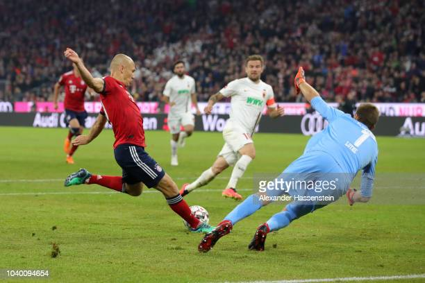 Arjen Robben of Bayern Munich scores his team's first goal past Andreas Luthe of Augsburg during the Bundesliga match between FC Bayern Muenchen and...