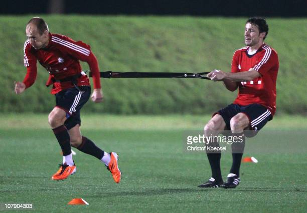 Arjen Robben of Bayern pulls Mark van Bommel of Bayern during the FC Bayern Muenchen training session at Aspire Academy for Sports Excellence...