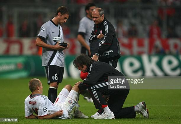 Arjen Robben of Bayern receives medical treatment by team doctor HansWilhelm MuellerWohlfahrt after picking an injury during the UEFA Champions...