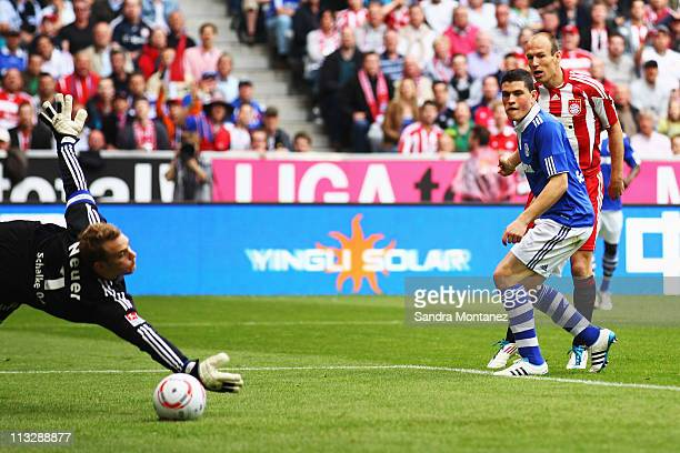 Arjen Robben of Bayern scores the opening goal against goalkeeper Manuel Neuer of Schalke during the Bundesliga match between FC Bayern Muenchen and...