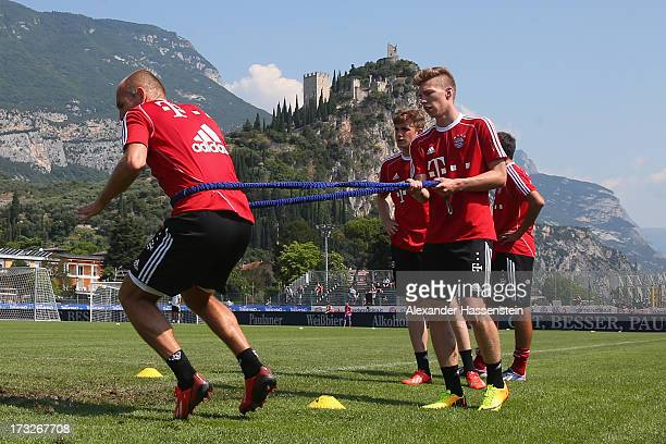 Arjen Robben of FC Bayern Muenchen and his team mate Mitchell Weiser during a training session at Campo Sportivo on July 11 2013 in Arco Italy