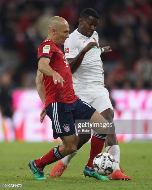 Arjen Robben of FC Bayern Muenchen fights for the ball with Sergio Cordova of FC Augsburg during the Bundesliga match between FC Bayern Muenchen and...