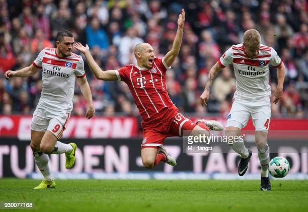 Arjen Robben of FC Bayern Muenchen is challenged by Rick van Drongelen of Hamburg during the Bundesliga match between FC Bayern Muenchen and...