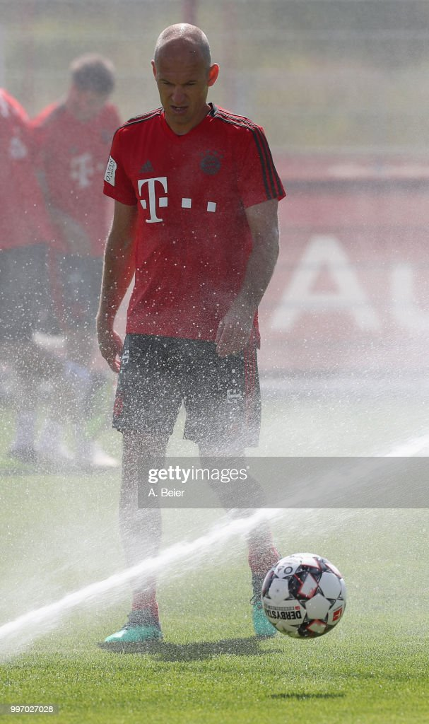 Arjen Robben of FC Bayern Muenchen is pictured as the lawn sprinkler turns on during a training session at the club's Saebener Strasse training ground on July 12, 2018 in Munich, Germany.