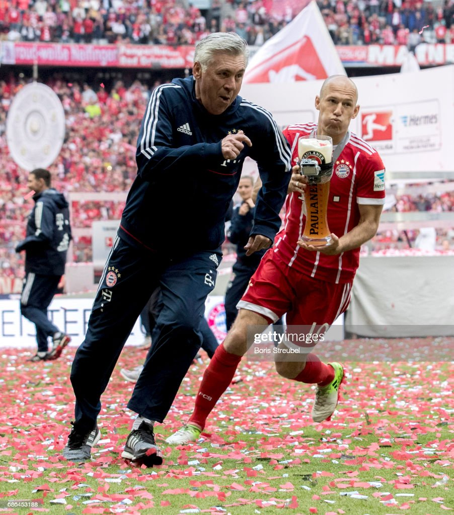 Arjen Robben of FC Bayern Muenchen tries to shower his head coach Carlo Ancelotti with beer in celebration of the 67th German Championship title following the Bundesliga match between Bayern Muenchen and SC Freiburg at Allianz Arena on May 20, 2017 in Munich, Germany.