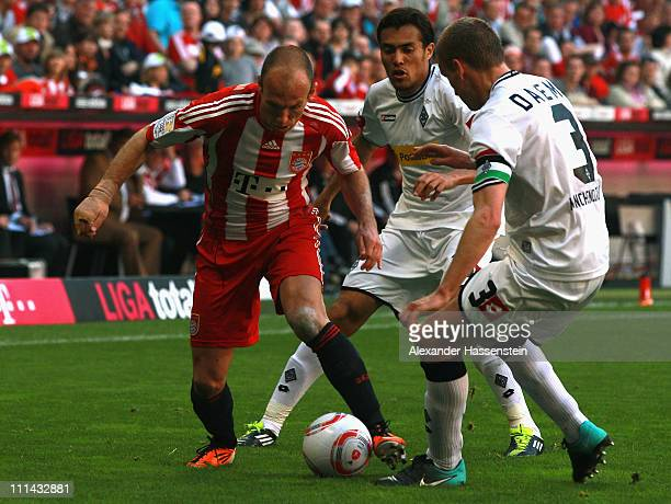 Arjen Robben of Muenchen battles for the ball with Filip Daems of Gladbach and his team mate Juan Arango during the Bundesliga match between FC...