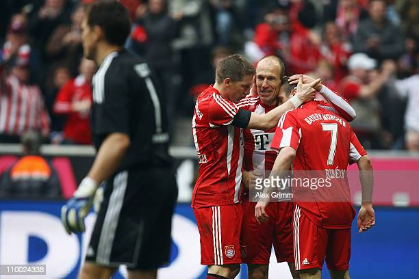 Arjen Robben of Muenchen celebrates his team's third goal with team mates Bastian Schweinsteiger and Franck Ribery as goalkeeper Frank Rost of...