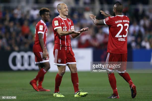 Arjen Robben of Muenchen celebrates his team's third goal with team mate Arturo Vidal during the friendly match between AlAhli and Bayern Muenchen on...