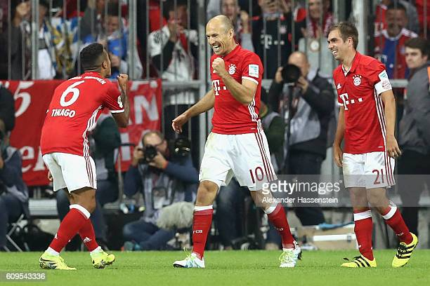 Arjen Robben of Muenchen celebrates scoring the 3rd team goal with his team mates Thiago and Philipp Lahm during the Bundesliga match between Bayern...