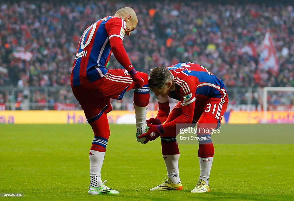 Arjen Robben (L) of Muenchen celebrates with team mate Bastian Schweinsteiger, who kisses his shoe after Robben scores his team's fourth goal during the Bundesliga match between FC Bayern Muenchen and Hamburger SV at Allianz Arena on February 14, 2015 in Munich, Germany.