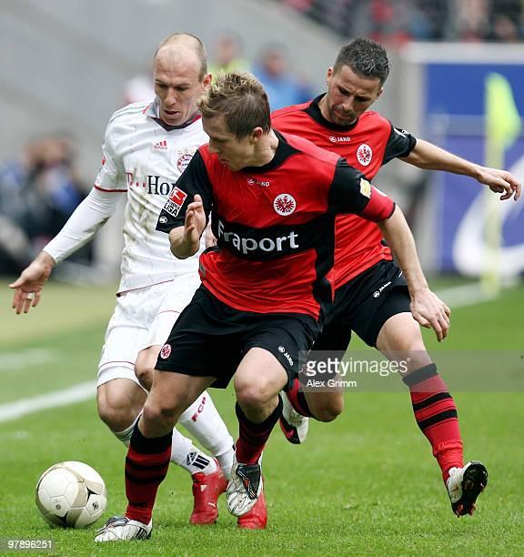 Arjen Robben of Muenchen is challenged by Christoph Spycher and Benjamin Koehler of Frankfurt during the Bundesliga match between Eintracht Frankfurt...