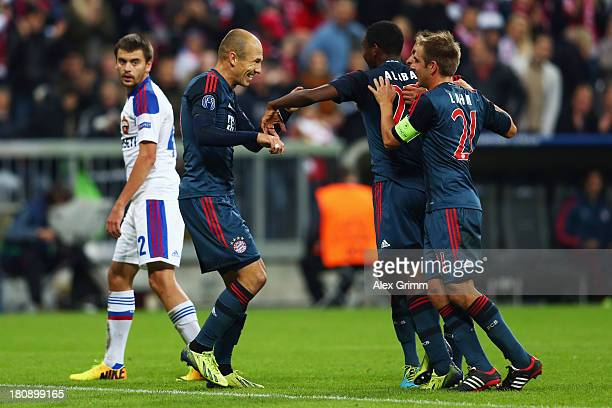 Arjen Robben of Muenchen scores his team's third goal with team mates David Alaba and Philipp Lahm during the UEFA Champions League Group D match...