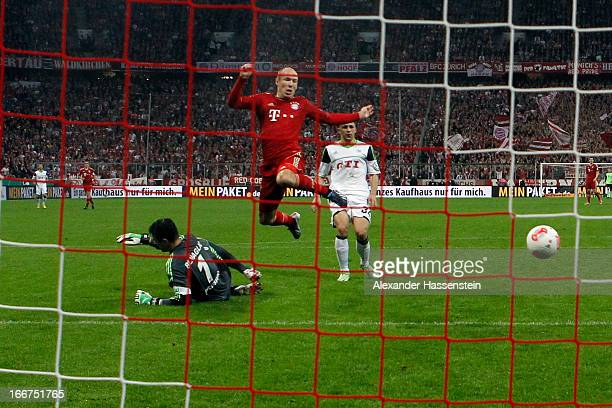 Arjen Robben of Muenchen scores the 2nd team goal against keeper Siego Benaglio of Wolfsburg and his team mate Ricardo Rodriguez during the DFB Cup...