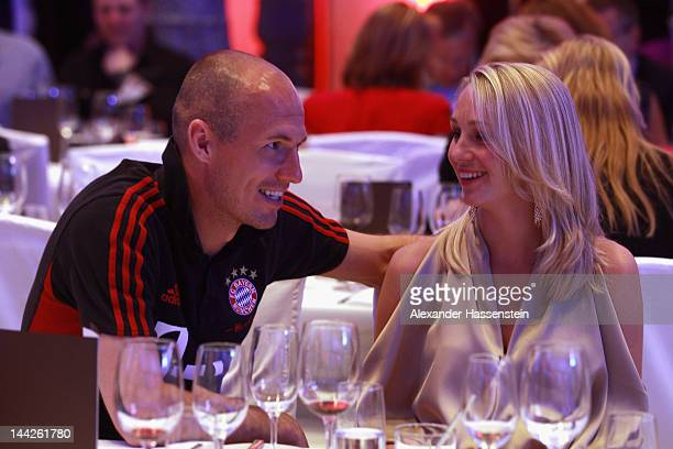 Arjen Robben of Muenchen talks to his wife Bernadien Robben during the Bayern Muenchen party at Telekom representative office on May 13 2012 in...
