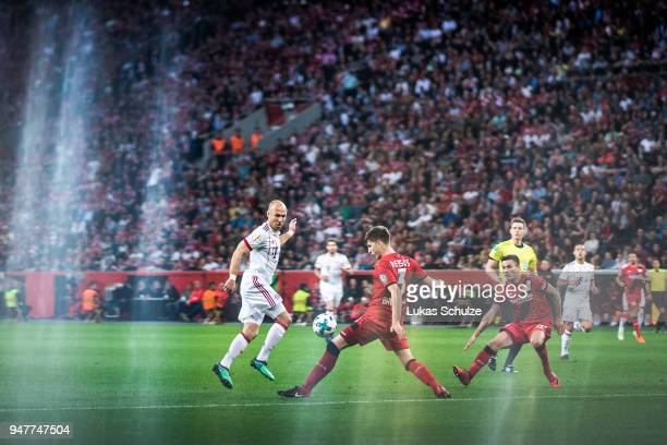 Arjen Robben of Munich and Panagiotis Retsos of Leverkusen in action during the DFB Cup semi final match between Bayer 04 Leverkusen and Bayern...